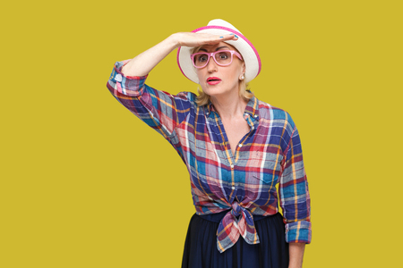 Looking for something so far. Portrait of attentive modern stylish mature woman in casual style with hat and eyeglasses standing with hand on forehead. indoor studio shot isolated on yellow background