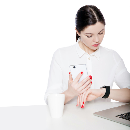 Portrait of attractive brunette businesswoman in white shirt sitting, holding smartphone mobile and looking at display of her smartwatch and reading something. studio shot isolated in white background