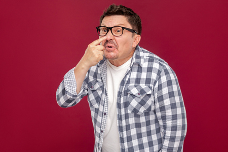 Portrait of middle aged business man in casual checkered shirt and eyeglasses standing and showing lie gesture touching his nose.