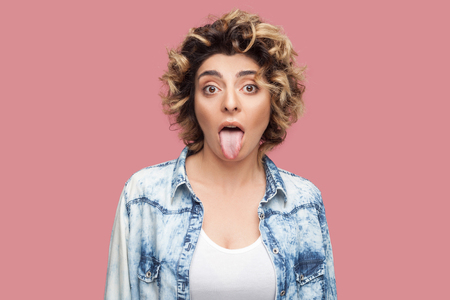 Portrait of crazy or shocked funny young woman with curly hairstyle in casual blue shirt standing, tongue out and looking at camera with big eyes. indoor studio shot, isolated on pink background.