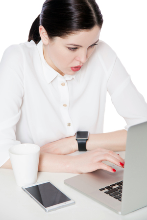 Top view portrait of attentive serious attractive brunette businesswoman in shirt sitting with laptop and looking at display and reading something. indoor studio shot, isolated in white background. Stock Photo