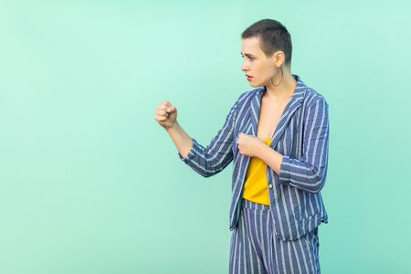 Profile side view portrait of serious beautiful short hair young stylish woman in casual striped suit standing with boxing fists and looking at camera. studio shot isolated on light green background.