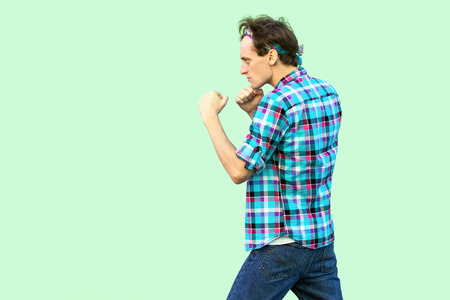 Profile side view portrait of angry young man in casual checkered shirt and headband standing and looking at camera with boxing fists and ready to attack. studio shot, isolated on green background.