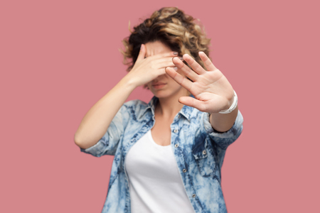 Stop, I don't want to look at this. Portrait of confused or scared young woman with curly hair standing covering her eyes and showing stop sign. indoor studio shot, isolated on pink background. Banco de Imagens