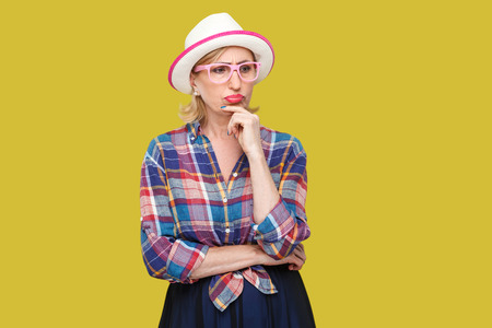 Portrait of serious pensive modern stylish mature woman in casual style with hat and eyeglasses standing, looking away and pondering doubtful. indoor studio shot isolated on yellow background.