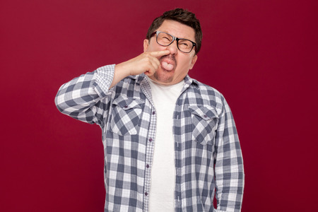 Portrait of funny crazy handsome middle aged business man in casual checkered shirt and eyeglasses standing, drilling his nose and tongue out. indoor studio shot, isolated on dark red background.