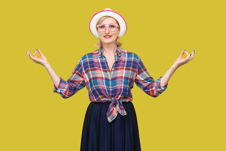 Portrait of calm modern stylish mature woman in casual style with hat and eyeglasses standing with raised arms, smiling, doing yoga pose exercises. indoor studio shot isolated on yellow background.