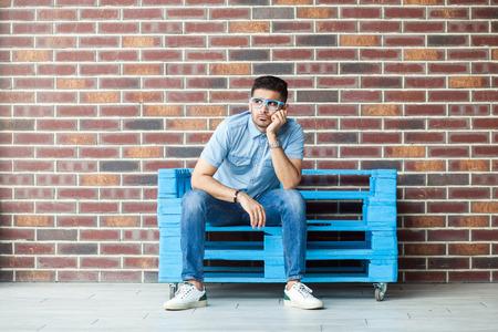 Volledig portret van een doordachte serieuze knappe jonge bebaarde man in casual stijl en bril zittend op een blauwe houten pallet, denkend en wegkijkend. indoor studio opname op bruine bakstenen muur.