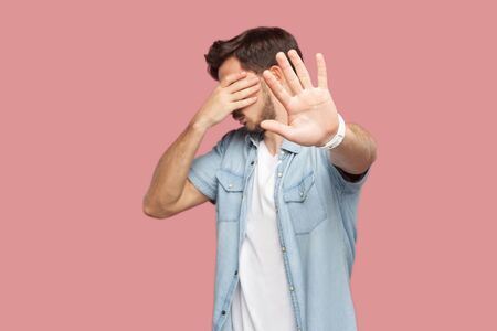 Stop, I don't want to see this. Portrait of bearded young man in blue casual style shirt standing, covering his eyes and showing stop hand sign gesture. indoor studio shot, isolated on pink background