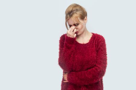 Portrait of sad alone or tired beautiful young blond woman in red blouse standing, holding head down and crying with trouble and hopeless. indoor studio shot isolated on light gray background.