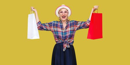 Love shopping! Satisfied modern grandma in white hat and in checkered shirt holding shopping bags and triumphing with raised arms and toothy smile. Indoor, studio shot isolated on yellow background. 免版税图像
