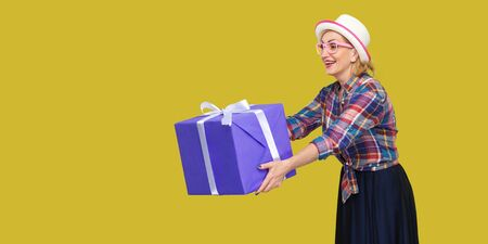 Side view portrait of happy beautiful fancy grandma in white hat and in checkered shirt standind, sharing, giving you big gift box with toothy smile. indoor studio shot isolated on yellow background.