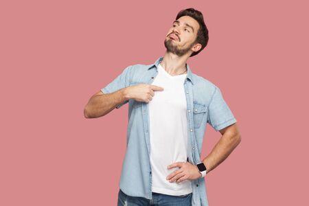 Este soy yo. Retrato de orgulloso altivo guapo barbudo joven en camisa azul estilo casual de pie, mirando a otro lado y apuntando a sí mismo. tiro del estudio de interior, aislado en fondo rosado.