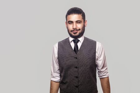 Portrait of funny happy handsome bearded brunette man in white shirt and waistcoat standing, smiling and winking and looking at camera. indoor studio shot isolated on gray background.