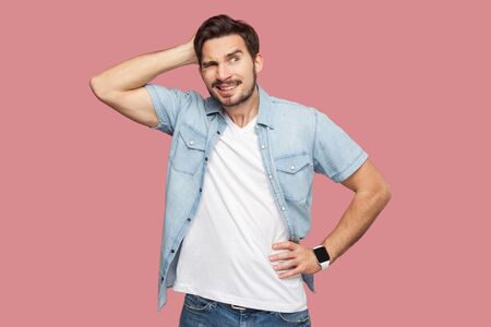 Portrait of query handsome bearded young man in blue casual style shirt standing and looking away and thinking what to do. indoor studio shot, isolated on pink background.