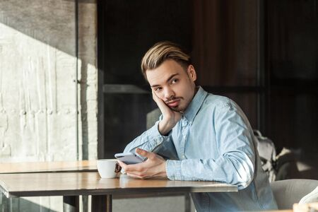 Portrait of handsome thoughtful bearded young man in blue denim shirt sitting in cafe and drinking coffee, tired for waiting friend for meeting or thinking, looking away. indoor, lifestyle