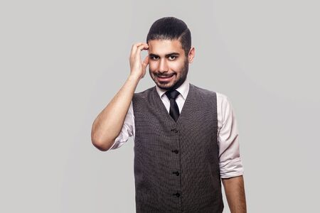 Portrait of thoughtful handsome bearded brunette man in white shirt, waistcoat standing scratching his head, looking at camera and thinking what to do. indoor studio shot isolated on gray background. Stock Photo