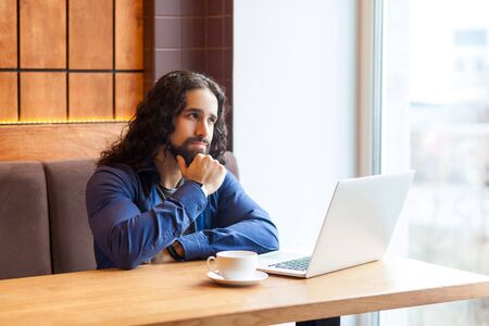 Portrait of wondering handsome bearded intelligence young adult man freelancer in casual style sitting in cafe and writting a book in laptop, bussinessman in office. Indoor, lifestyle concept
