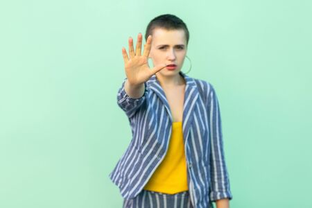 Stop. Portrait of serious handsome beautiful short hair young stylish woman in casual striped suit standing blocking and showing stop hand sign. indoor studio shot isolated on light green background.