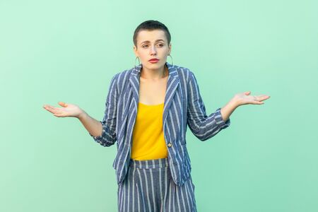 I don't know. Portrait of confused handsome beautiful short hair young stylish woman in casual striped suit standing with raised arms, thinking. indoor studio shot isolated on light green background.