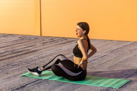 Young sporty girl in black sportwear sitting on mat and have a strong hurt problem with back, spasm painful. Gripping spinal with hand and screaming. Outdoor, Sport injury healthy medical concept Stock Photo