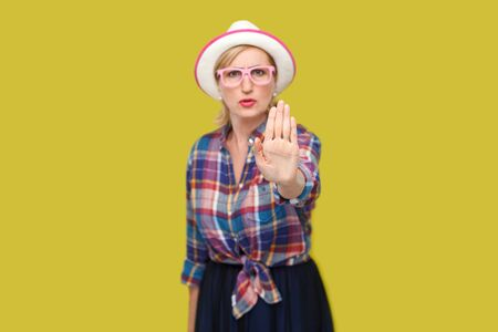 Portrait of angry or scared modern stylish mature woman in casual style with hat and eyeglasses standing with stop hand sign gesture.