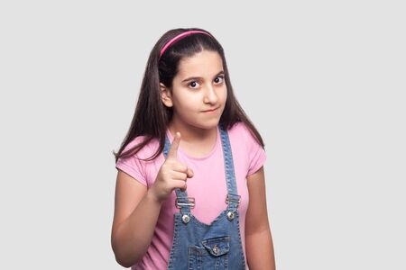 Portrait of serious beautiful brunette young girl in casual style, pink t-shirt and blue denim overalls standing, looking and warning at camera. indoor studio shot, isolated on light gray background.