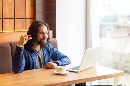 Please little bit! Portrait of cunning young adult man freelancer in casual style sitting in cafe with laptop, looking at camera, showing with finger to make less loud music. Indoor, lifestyle concept