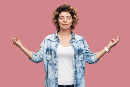 Portrait of calm young woman with curly hairstyle in casual blue shirt standing with closed eyes, raised arms, smile and doing yoga meditating. indoor studio shot, isolated on pink background.