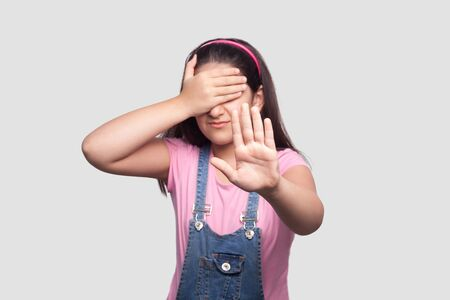 I don't want to look at this. Portrait of scared or shy girl in pink t-shirt and blue denim overalls standing, covering her eyes and showing stop sign. indoor studio shot, isolated on gray background.