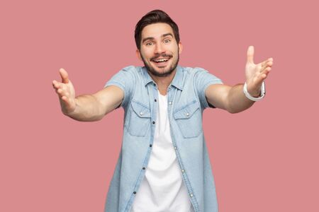 Portrait of happy handsome bearded young man in blue casual style shirt standing with raised arms, want to hug and looking at camera with toothy smile. indoor studio shot, isolated on pink background.
