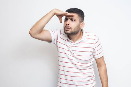 Portrait of attentive handsome bearded young man in striped t-shirt standing with hand on forehead and trying to look at something far. indoor studio shot, isolated on white background.