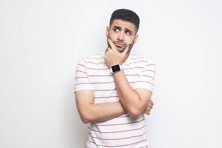 Portret van een peinzende knappe bebaarde jongeman in een gestreept t-shirt die staat, zijn gezicht aanraakt, wegkijkt en ergens aan denkt. indoor studio opname, geïsoleerd op een witte achtergrond. Stockfoto