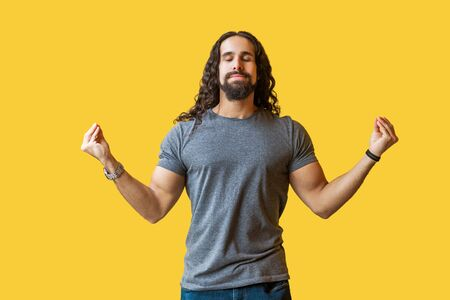 Yoga time. Portrait of calm serious bearded young man with long curly hair in grey tshirt standing in yoga pose and meditating with closed eyes and relaxed. studio shot isolated on yellow background. Stock Photo