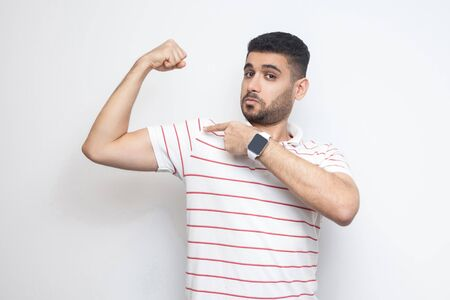 I am strong. Portrait of proud handsome bearded young man in striped t-shirt standing, pointing at his bicep and looking at camera with satisfied face. indoor studio shot, isolated on white background