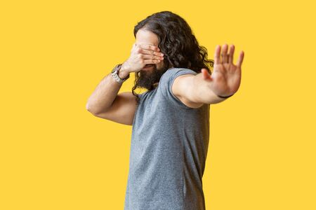 I don't want to look at this. Portrait of afraid or shy young man with long curly hair in grey tshirt closing his eyes and showing stop hand gesture. indoor studio shot isolated on yellow background.