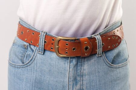 Man standing in blue jeans and brown leather handmade belt, closeup. indoor studio shot, isolated on grey background.