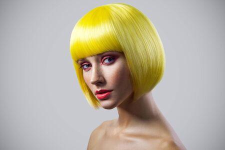 Ritratto di bellezza di giovane modello femminile calmo carino con lentiggini, trucco rosso e parrucca gialla che guarda l'obbiettivo con la faccia seria. girato in studio al coperto, isolato su sfondo grigio.