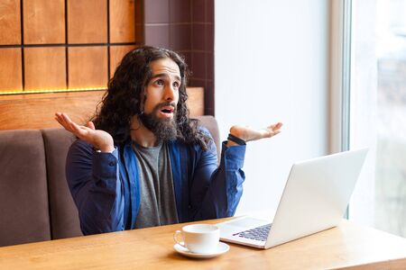 I dont no!Portrait of confused handsome young adult man freelancer in casual style sitting in cafe with laptop, raised hands and showing unknown gesture, looking up. Indoor, lifestyle concept Stock Photo