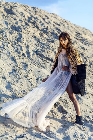 Brunette woman in translucent beach cover up with leopard fur coat posing on sandy beach at sunset. standing, looking at camera. wind fluttering her long dress. Fashion outdoor shot in the summertime.
