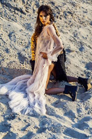 Attractive brunette woman in translucent beach cover up with leopard fur coat and black boots posing on sandy beach at sunset. looking at camera. Fashion outdoor shot in the summertime.