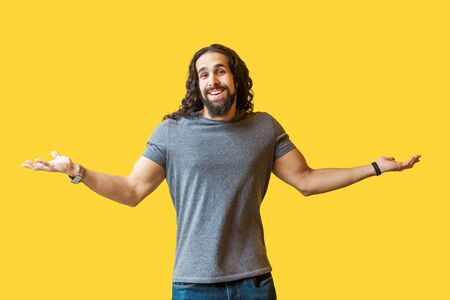 I don't know. Portrait of thinking bearded young man with long curly hair in grey tshirt standing with raised arms and looking at camera with confused face. studio shot isolated on yellow background.