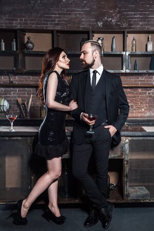 Coquetea en una fiesta. Chica sosteniendo vasos de vid y mirando con pasión al hombre barbudo. Foto de estudio, pared de ladrillo