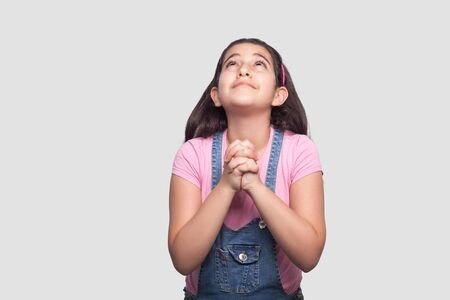 My God help me. Portrait of hopeful sad brunette young girl in pink t-shirt and blue denim overalls standing, looking up and praying or pleading. indoor studio shot isolated on light gray background