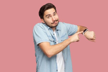 Portrait of sad handsome bearded young man in blue casual style shirt standing pointing and showing his smart watch and looking at camera. indoor studio shot, isolated on pink background.