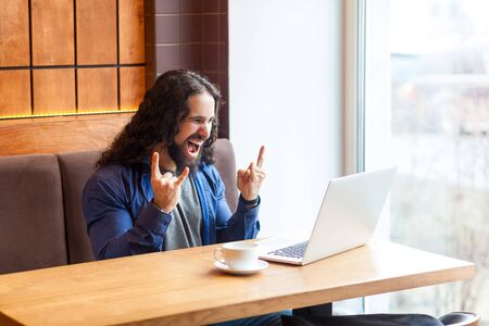 Yes! Portrait of happy handsome young adult man freelancer in casual style sitting in cafe and talking with friend in laptop, showing rock and roll sign with opened mouth. Indoor, lifestyle concept Stock Photo