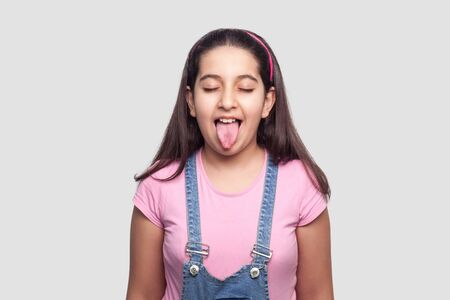 Portrait of funny beautiful brunette young girl in casual style, pink t-shirt and blue denim overalls standing with tongue out and closed eyes. indoor studio shot, isolated on light gray background. Фото со стока