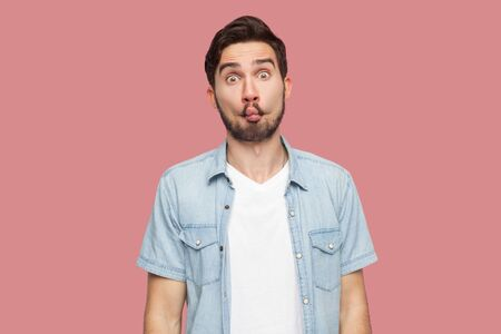 Portrait of funny comic face handsome bearded young man in blue casual style shirt standing with fish lips and looking at camera. indoor studio shot, isolated on pink background.