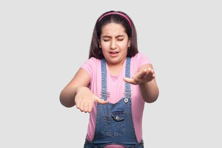 Portrait of closed eyes blind brunette young girl in casual pink t-shirt and blue denim overalls standing and try to touch or find something . indoor studio shot, isolated on light gray background.