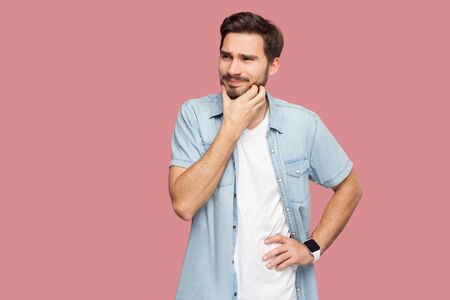 Portrait of confused handsome bearded young man in blue casual style shirt standing scratching beard and thinking what to do or try to find answer. indoor studio shot, isolated on pink background.